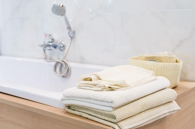 Serviette blanche se trouve sur la baignoire dans la salle de bain en arrière-plan