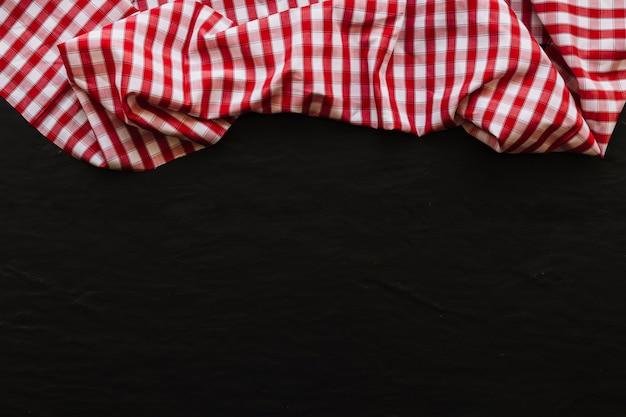 Serviette à carreaux drapée sur fond noir