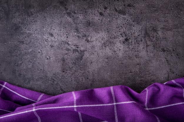 Serviette à carreaux violet vue de dessus sur une table en béton de cuisine sombre.