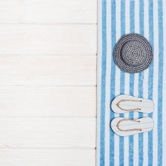 Serviette, chapeau de paille et pantoufles de plage