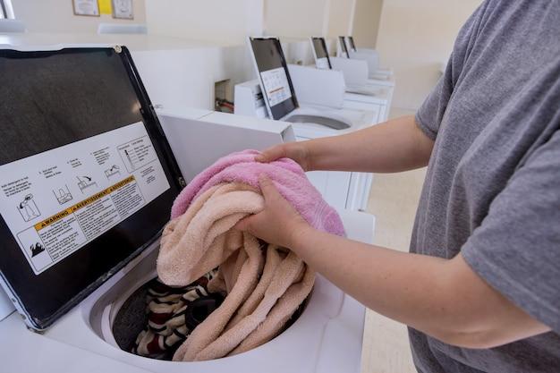 Serviette de chargement femme dans la machine à laver dans la buanderie