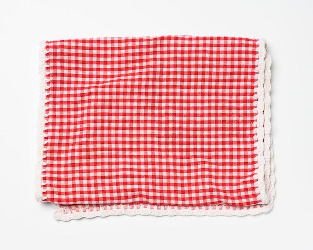 Serviette en coton plié à carreaux blanc rouge sur fond blanc