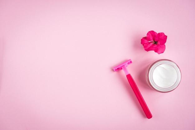 Serviette, crème, rasoir et fleur sur fond rose. mise à plat. soin de la peau.