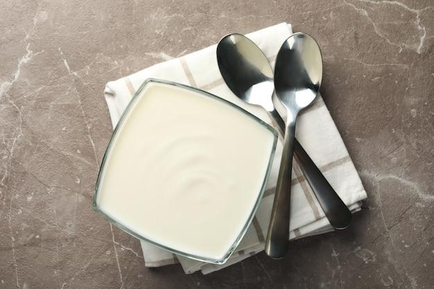 Serviette, cuillères et bol de crème sure sur fond gris, vue du dessus