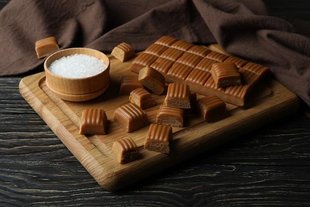 Serviette de cuisine et planche avec morceaux de caramel et sel sur table en bois