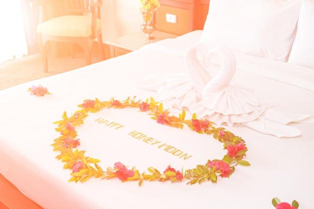 Serviette cygnes en forme de lit de luxe avec la lumière du soleil