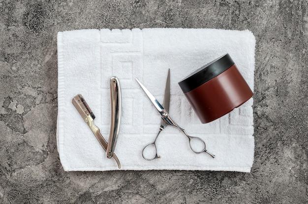 Sur une serviette dépliée en fond gris plâtre, elle est dotée d'un rasoir, de ciseaux et d'un gel coiffant. concept de rasage masculin, coupe de cheveux.