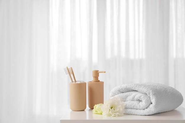 Serviette douce, brosses à dents et savon sur la table près de la fenêtre