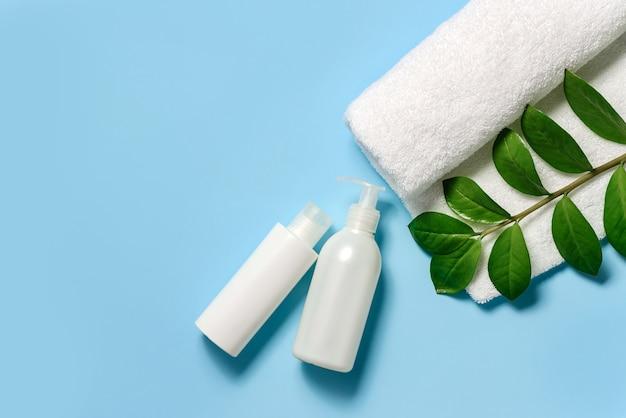 Une serviette éponge blanche, une branche verte et deux tubes de cosmétiques