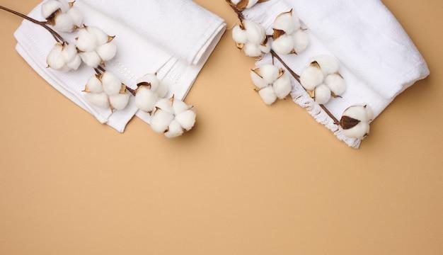 Serviette éponge en coton blanc plié et brins de fleur de coton sur fond marron clair, vue de dessus, espace pour copie