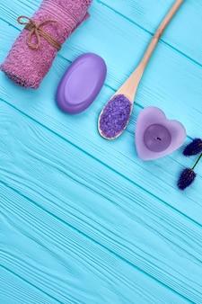Serviette éponge roulée avec savon et bougie sur un bureau en bois bleu. vue de dessus de tir vertical à plat.