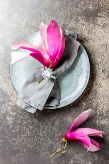 Serviette avec fleur de magnolia de printemps sur plaque grise