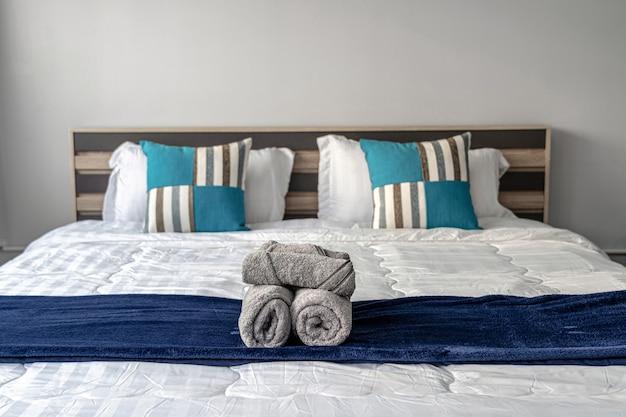 Serviette en gros plan sur un lit queen-size dans la chambre pour servir le client