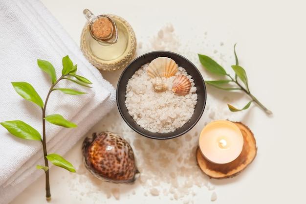 Serviette, huile de massage cosmétique, feuilles, sel de mer avec coquillages et bougie