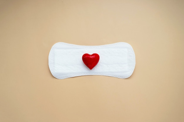 Serviette hygiénique pour femme avec coeur rouge. concept abstrait de la santé de la femme. serviettes menstruelles ou menstruelles.