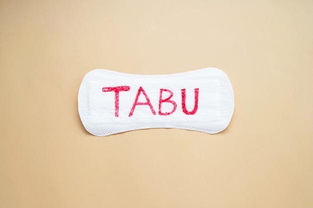 Serviette hygiénique pour femme avec mot tabu. concept social abstrait de la peur de parler de la période menstruelle