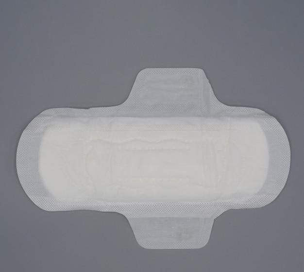 Serviette hygiénique. serviette hygiénique douce et confortable et fond gris. feuille supérieure blanche. studio tourné isolé. tampons en tissu pour la menstruation. type d'aile pour la nuit. absorbeur rapide. sensation de coton doux.