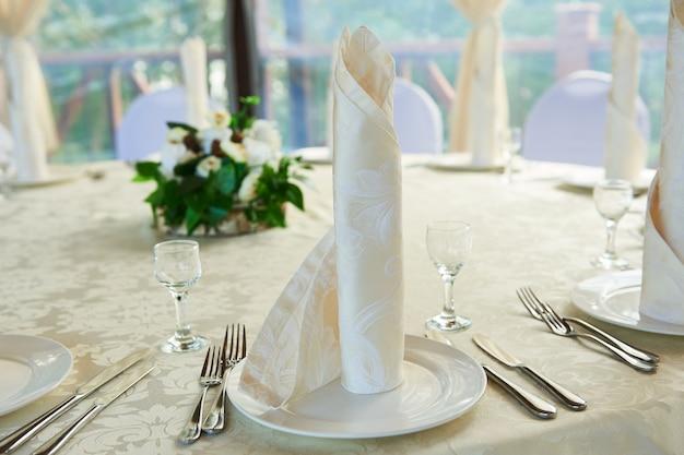 La serviette joliment pliée sur les assiettes, servant un banquet de fête