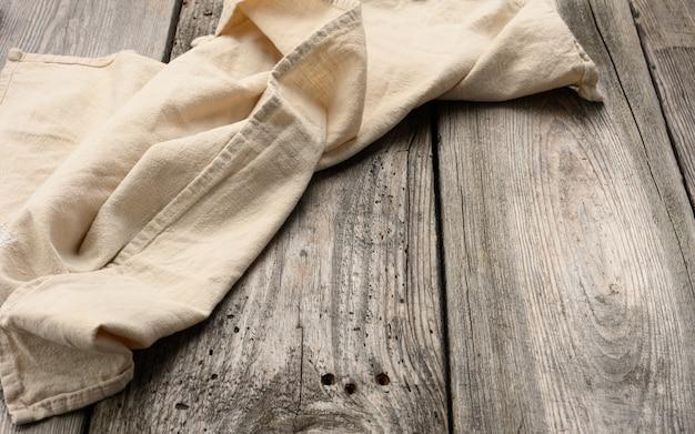 Serviette en lin beige pliée sur une table faite de vieilles planches de bois gris, vue du dessus, espace copie