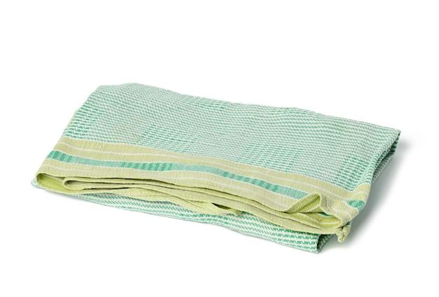 Serviette en lin vert plié sur fond blanc, vue de dessus