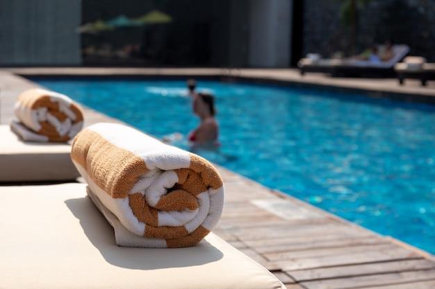 Serviette sur lit de bronzage avec femme dans la piscine en vacances d'été.