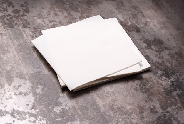 Serviette en papier blanc sur fond de table en pierre grise.