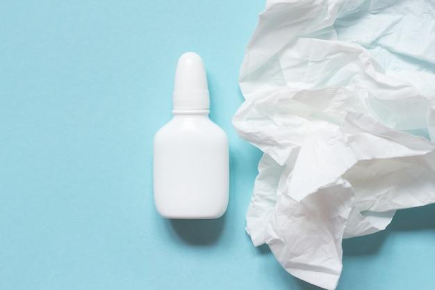 Serviette en papier froissé et gouttes nasales. concept grippe, rhume, écoulement nasal