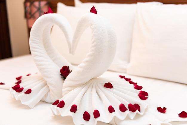 Serviette pliée cygne blanc, symboles de mariage sur lit blanc