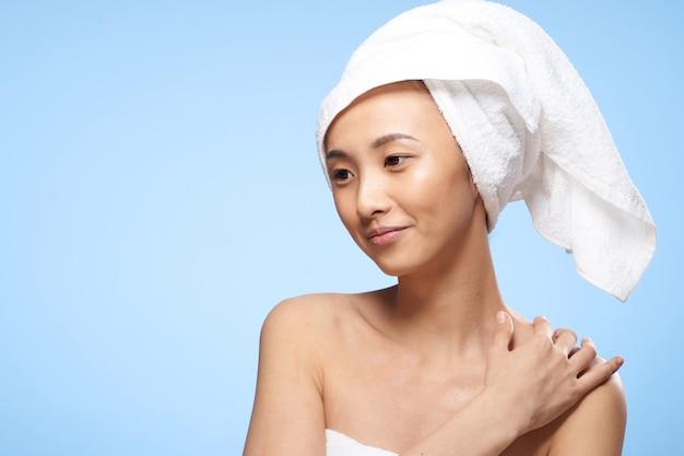 Serviette de soins de la peau propre jolie femme asiatique sur la tête bleue