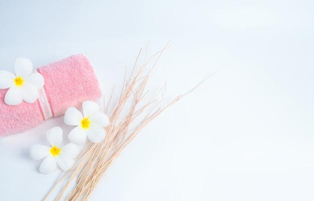 Serviette de spa rose roulée et fleurs de frangipanier avec branche