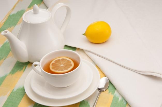 Sur une serviette tasse de thé au citron dans une soucoupe et théière