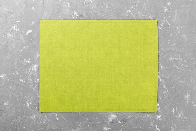 Serviette en tissu vert sur la vue de dessus de ciment rustique avec fond