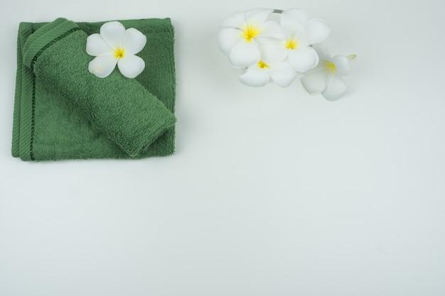 Serviette verte et fleur de plumaria sur le tableau blanc.