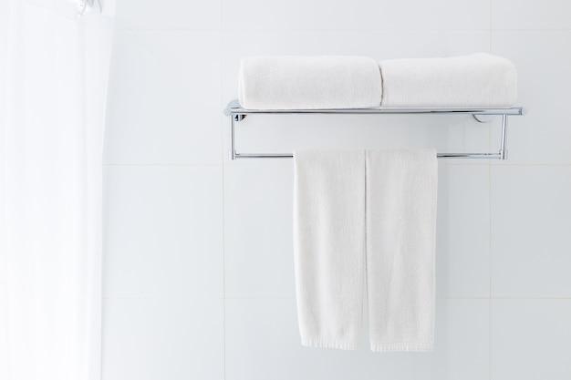 Serviettes de bain blanches suspendus sur le support dans une salle de bain blanche près de la douche