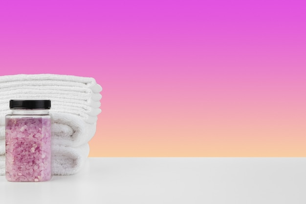 Serviettes de bain et sel de spa sur table blanche