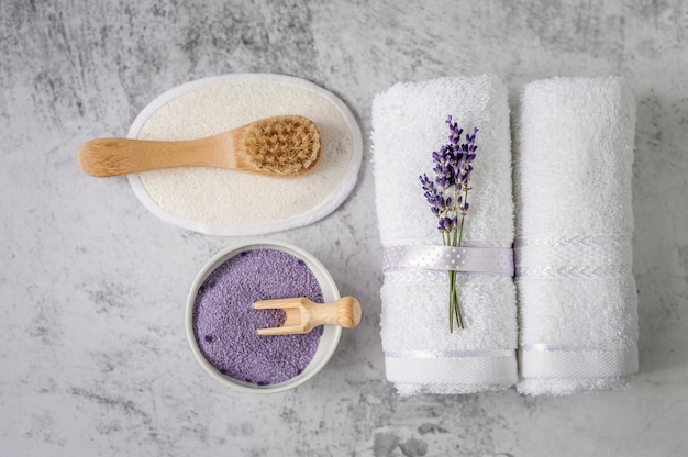 Serviettes de bain torsadées au sel de bain et pinceau gris clair. serviette de spa et ensemble d'accessoires de salle de bains contre un mur texturé. minimalisme, flou artistique. spa.