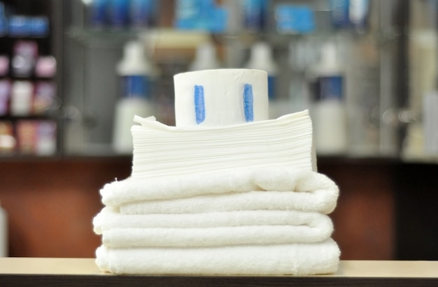 Serviettes blanches propres en coton pour coiffeur, serviettes en papier jetables, colliers de protection en papier avec bande adhésive pour la coiffure dans un salon de beauté.