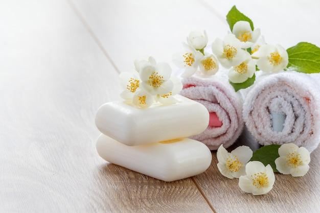 Serviettes blanches et savon pour les procédures de salle de bain avec des fleurs de jasmin sur des planches en bois avec espace de copie. produits et accessoires de spa