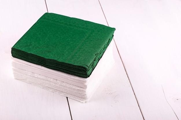 Serviettes blanches et vertes pour la table à manger sur une table en bois clair