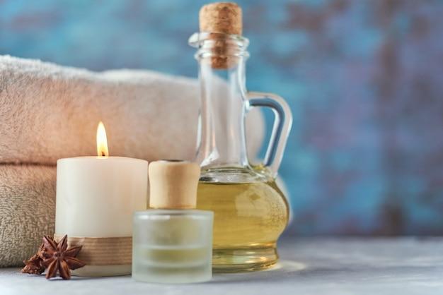 Serviettes, bougie et huile de massage sur table blanche