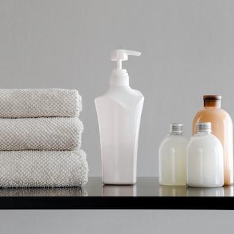 Serviettes, bouteilles avec shampoing, revitalisant, lait de douche et savon artisanal.