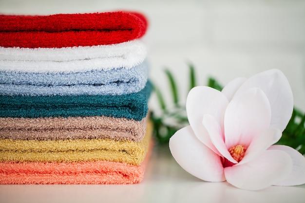 Des serviettes et une branche d'orchidée sur un fond blanc,
