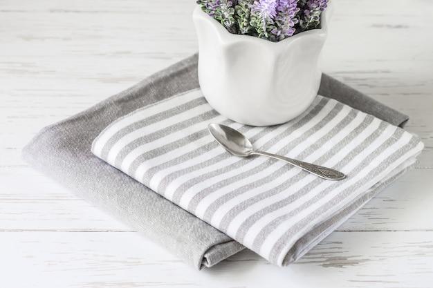 Serviettes de cuisine grises sur une table en bois blanche avec des fleurs