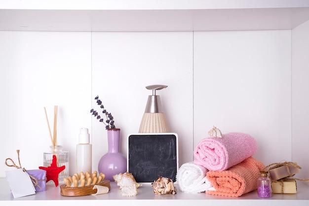 Serviettes dans un plateau en bois avec des baguettes aromatiques, des bougies, des coquillages, des débarbouillettes de massage