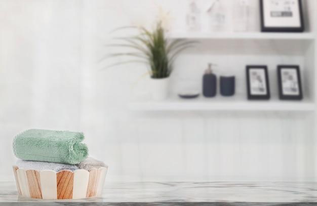 Serviettes dans un seau en bois sur une table en marbre dans une salle de bains blanche avec espace de copie.