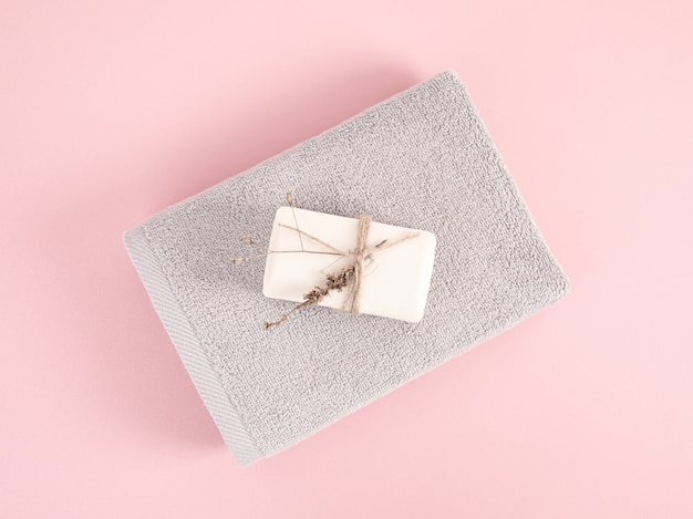 Serviettes éponge pliées et empilées avec du savon sur le fond rose