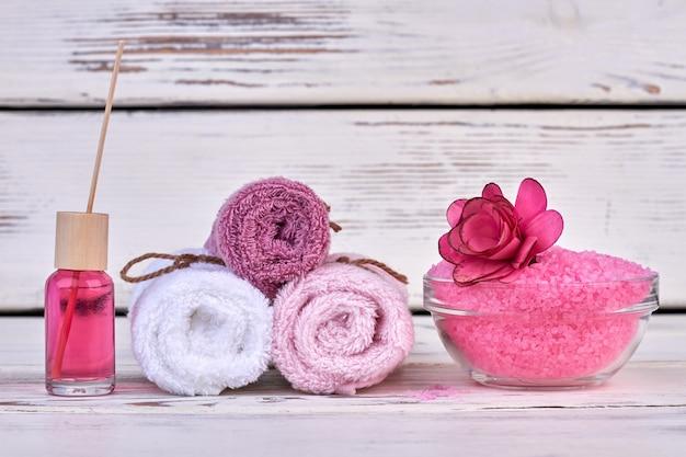 Serviettes éponge roulées nature morte avec sel rose et huile corporelle