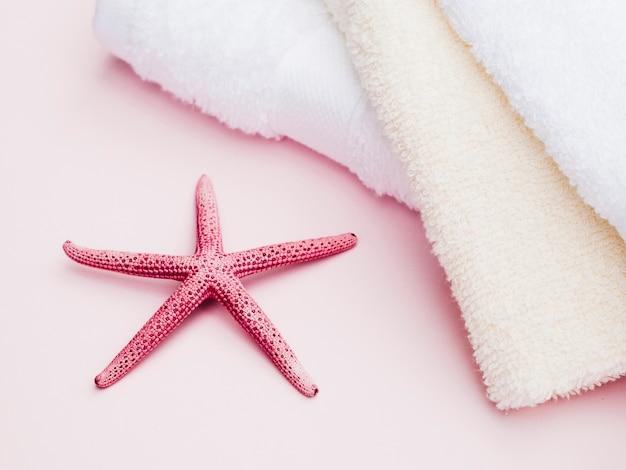 Serviettes et étoiles de mer sur fond rose