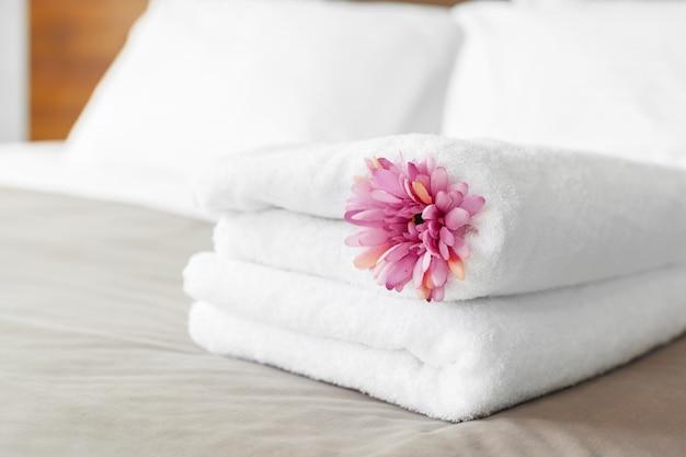 Serviettes et fleurs sur le lit dans la chambre d'hôtel
