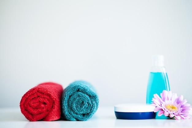 Serviettes et gel douche sur une table blanche dans la salle de bain.